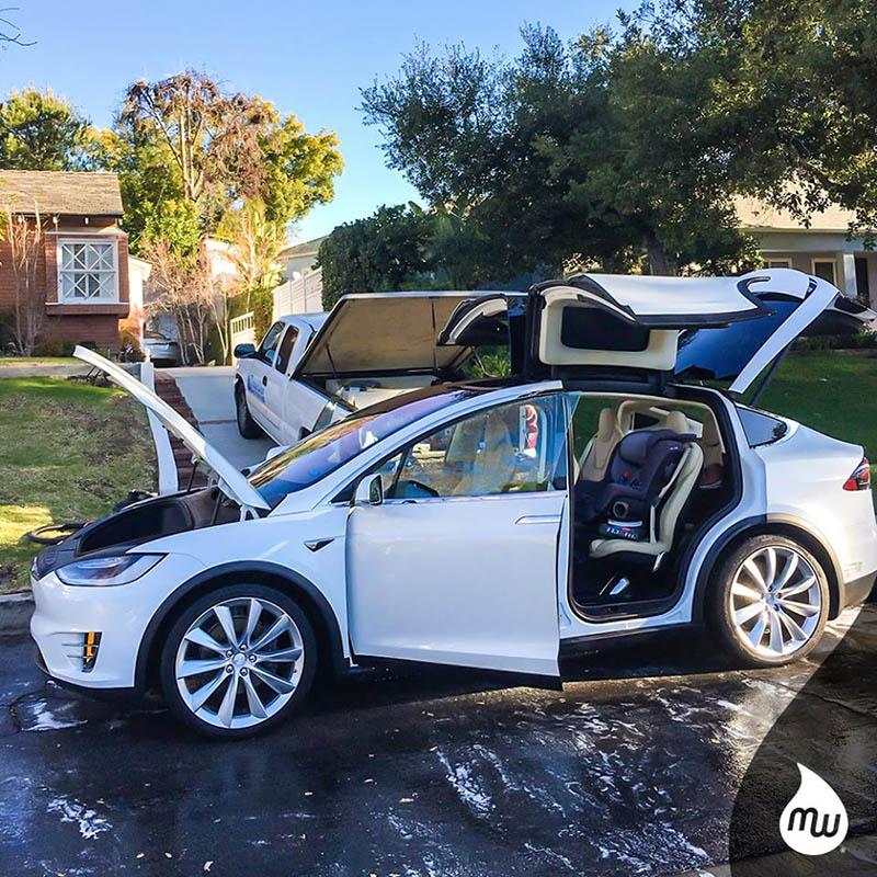 A white Tesla automobile in the middle of a MobileWash auto detailing and car cleaning service.
