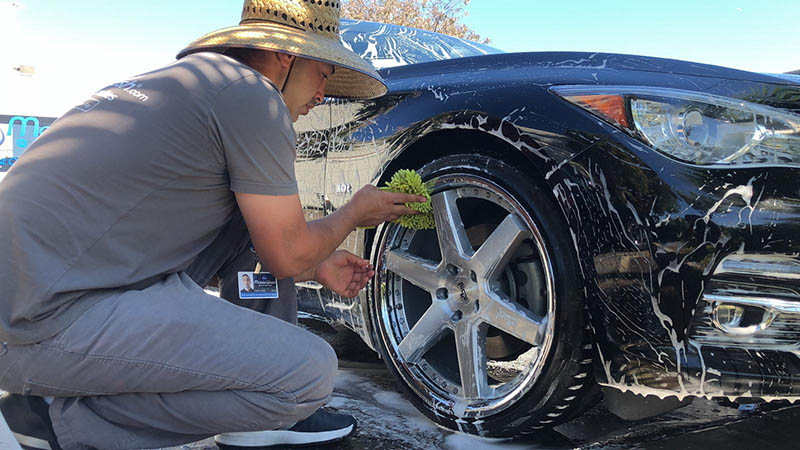 A MobileWash washer doing a tire-dressing for a black BMW for a car cleaning and mobile car detailing service.