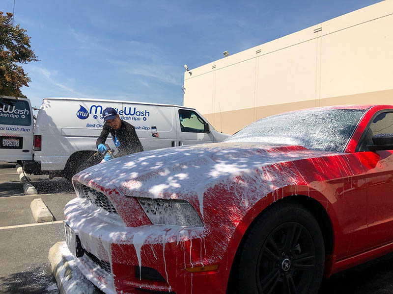 A MobileWash washer sprays soap foam on a red Ford Mustang with black rims for a car cleaning and auto detailing.